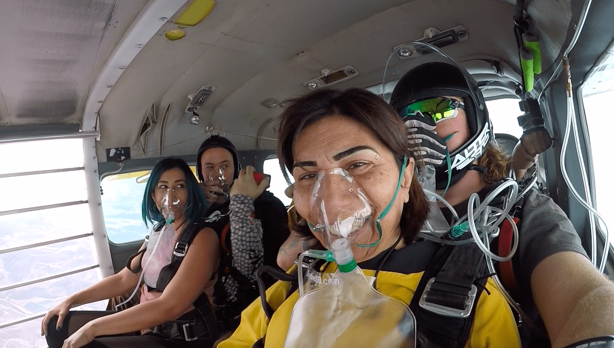 skydivers on airplane with oxygen masks on